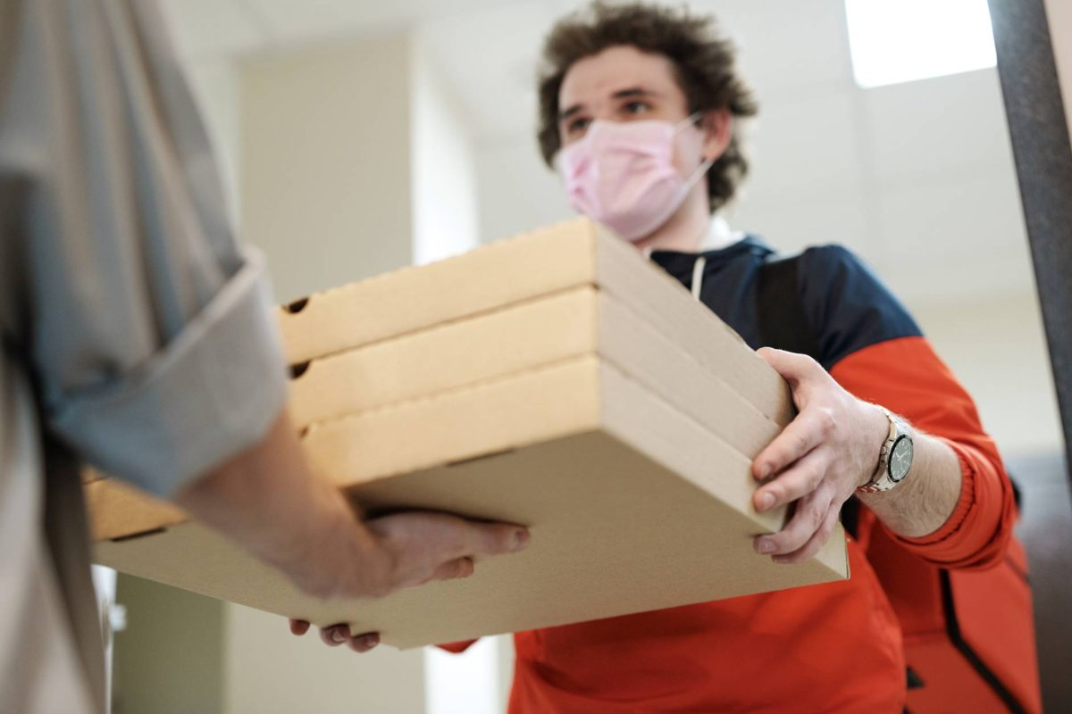 man wearing a face mask delivering pizza