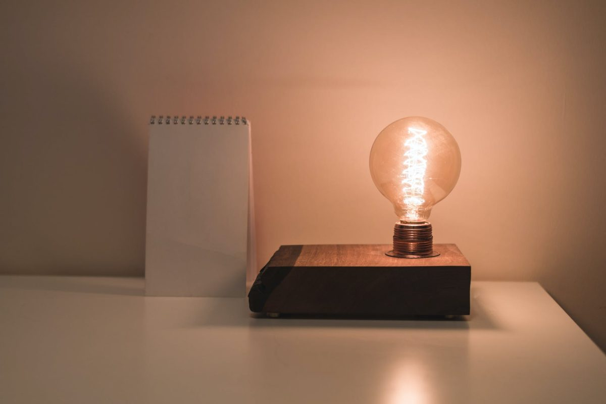 clear bulb beside white notepad on white surface