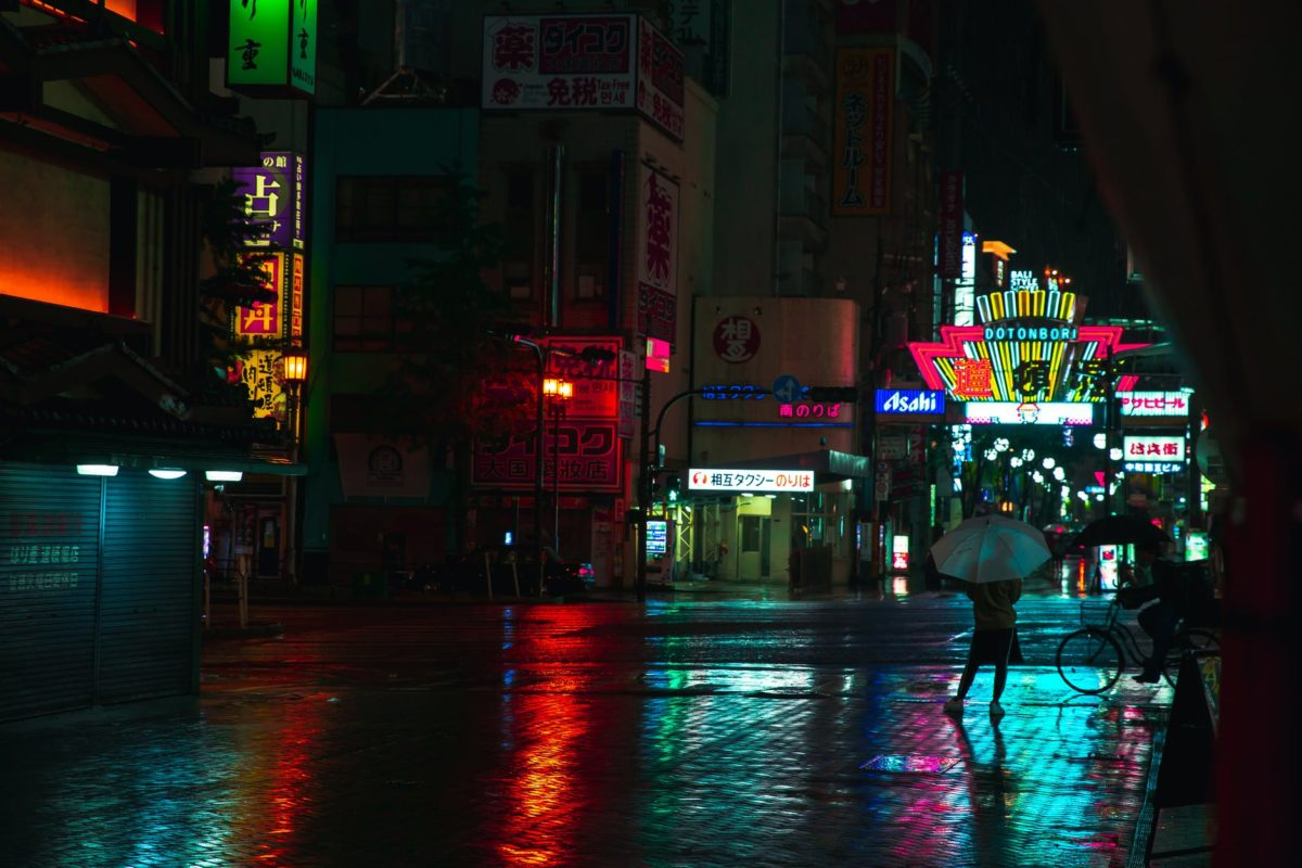 unrecognizable people on wet pavement in night asian city