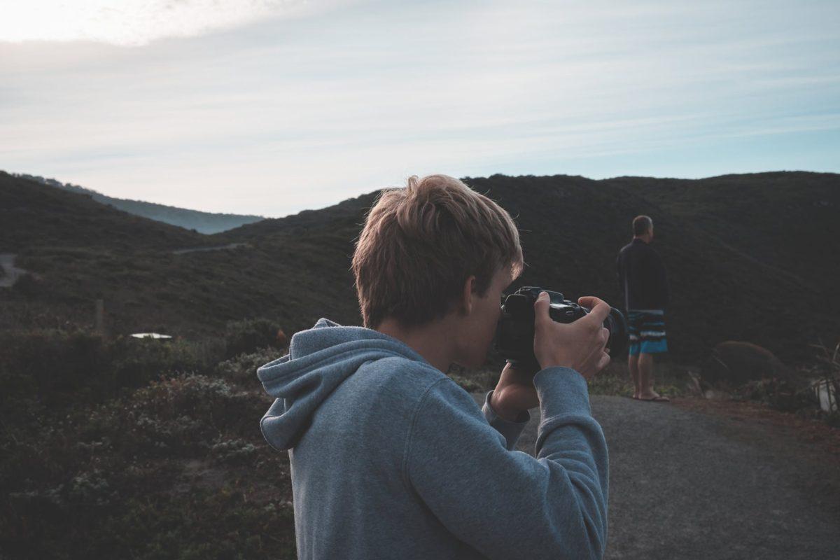 man taking photo of nature during trip