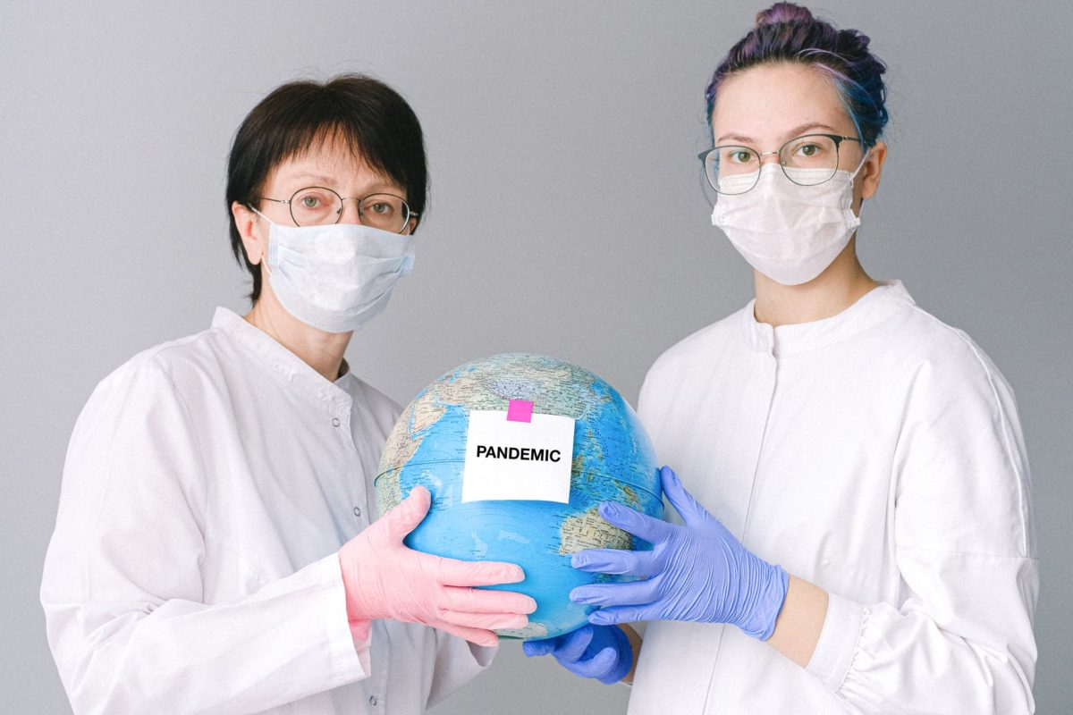 people with face masks and latex gloves holding a globe
