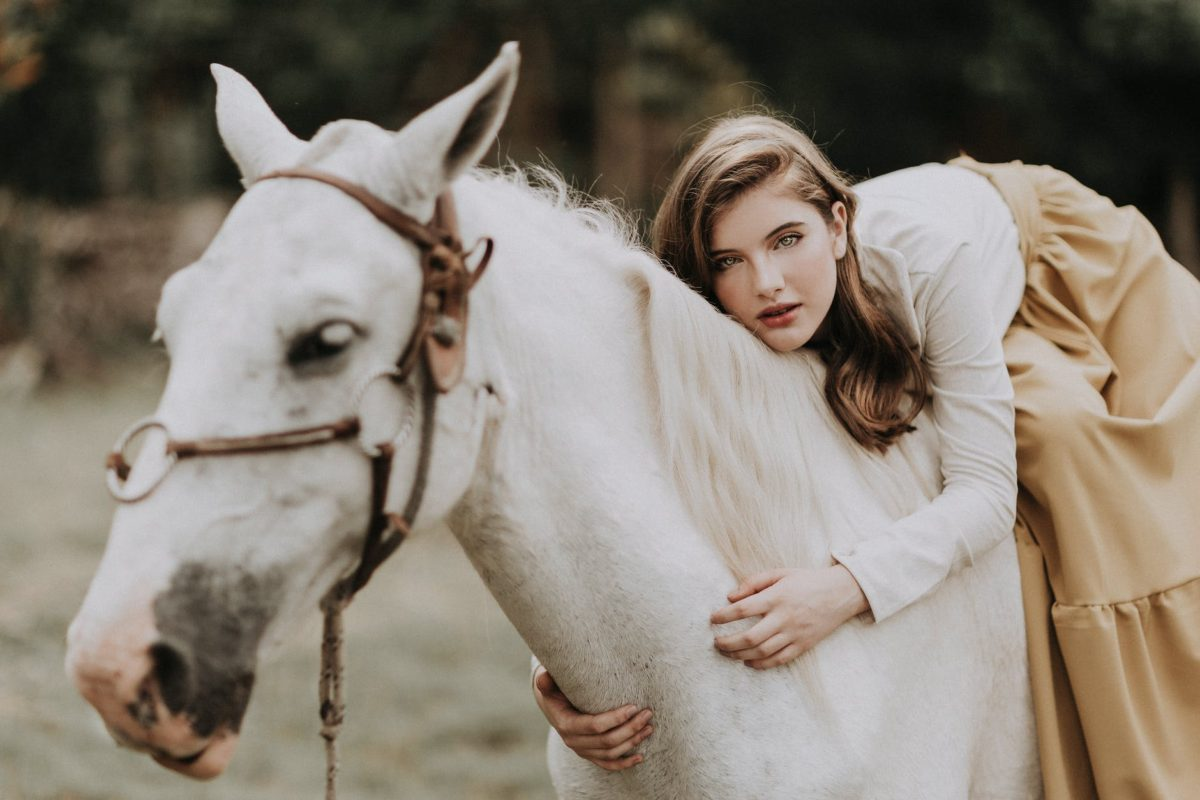 young woman lying on horse