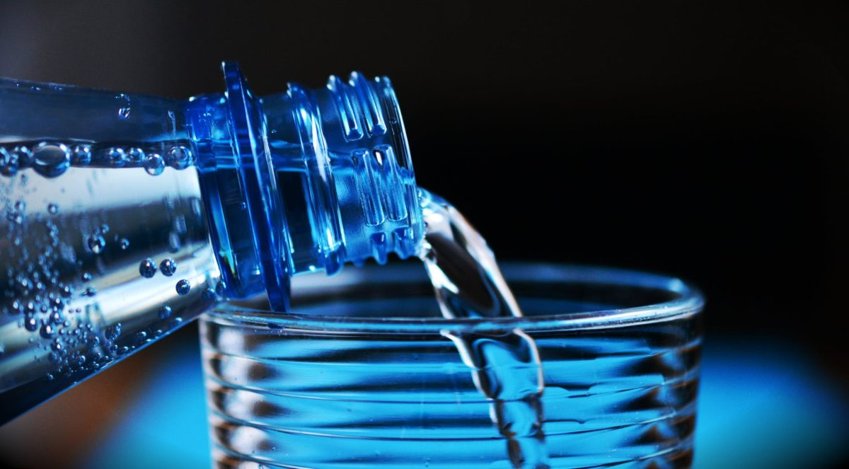close up of bottle pouring water on glass