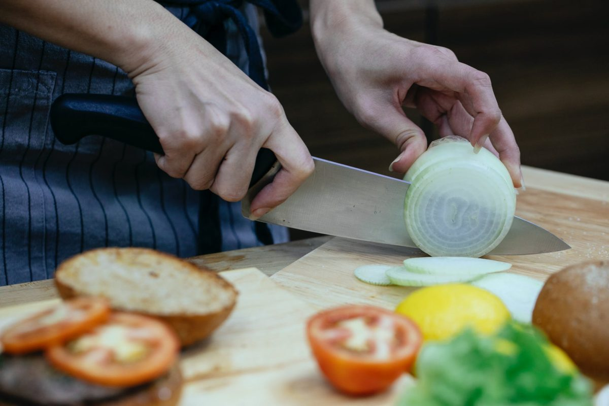 crop woman cutting onion in kitchen