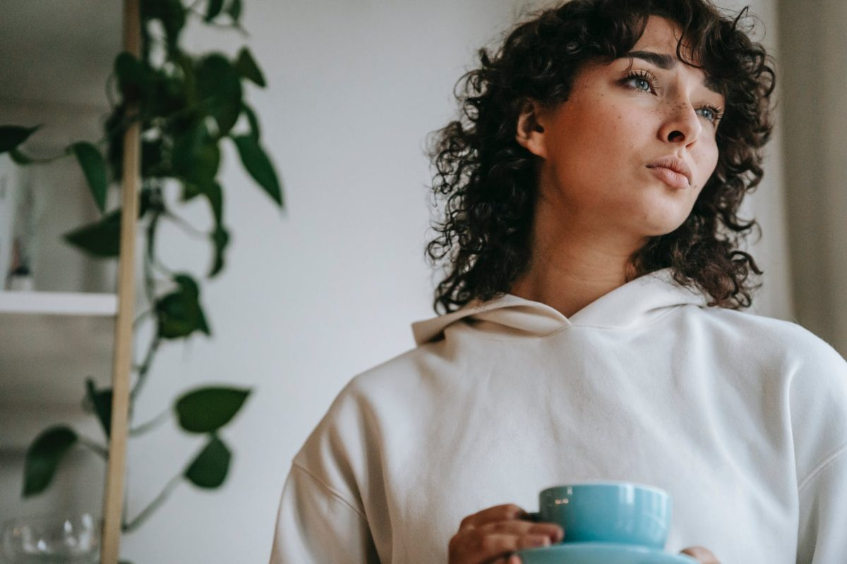 pensive woman with hot beverage at home