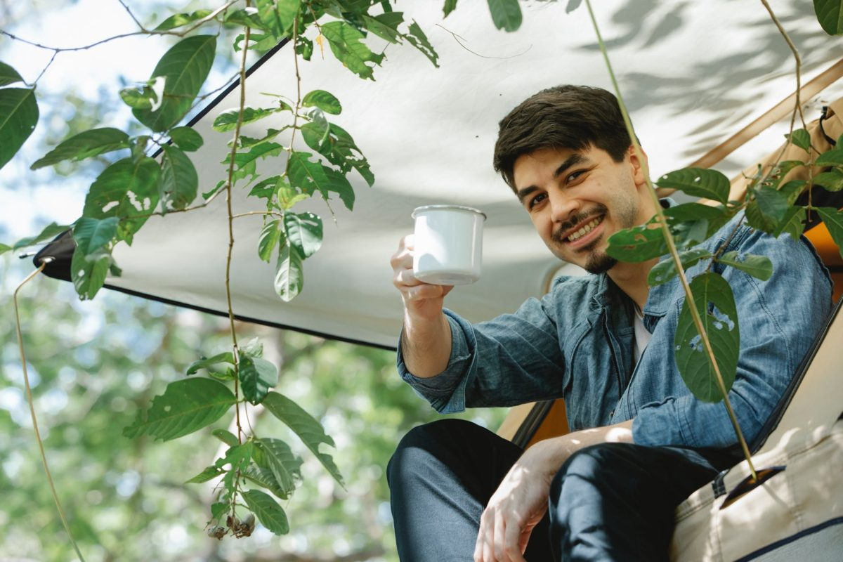 content young man enjoying beverage while recreating in tent during camping