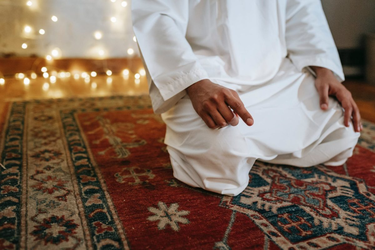 man in white thobe sitting on red and brown area rug