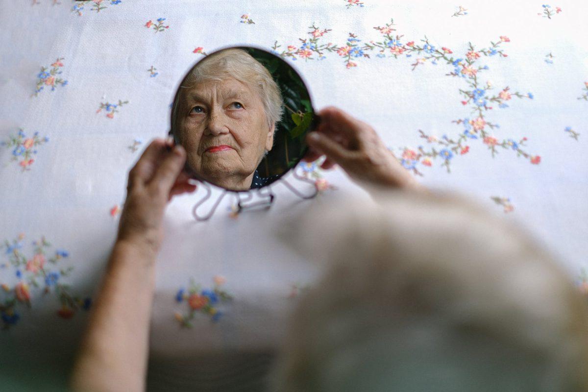 pensive elderly woman reflecting in mirror