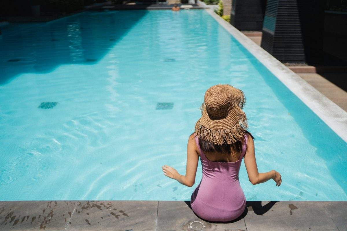 unrecognizable trendy woman relaxing at poolside in sunlight
