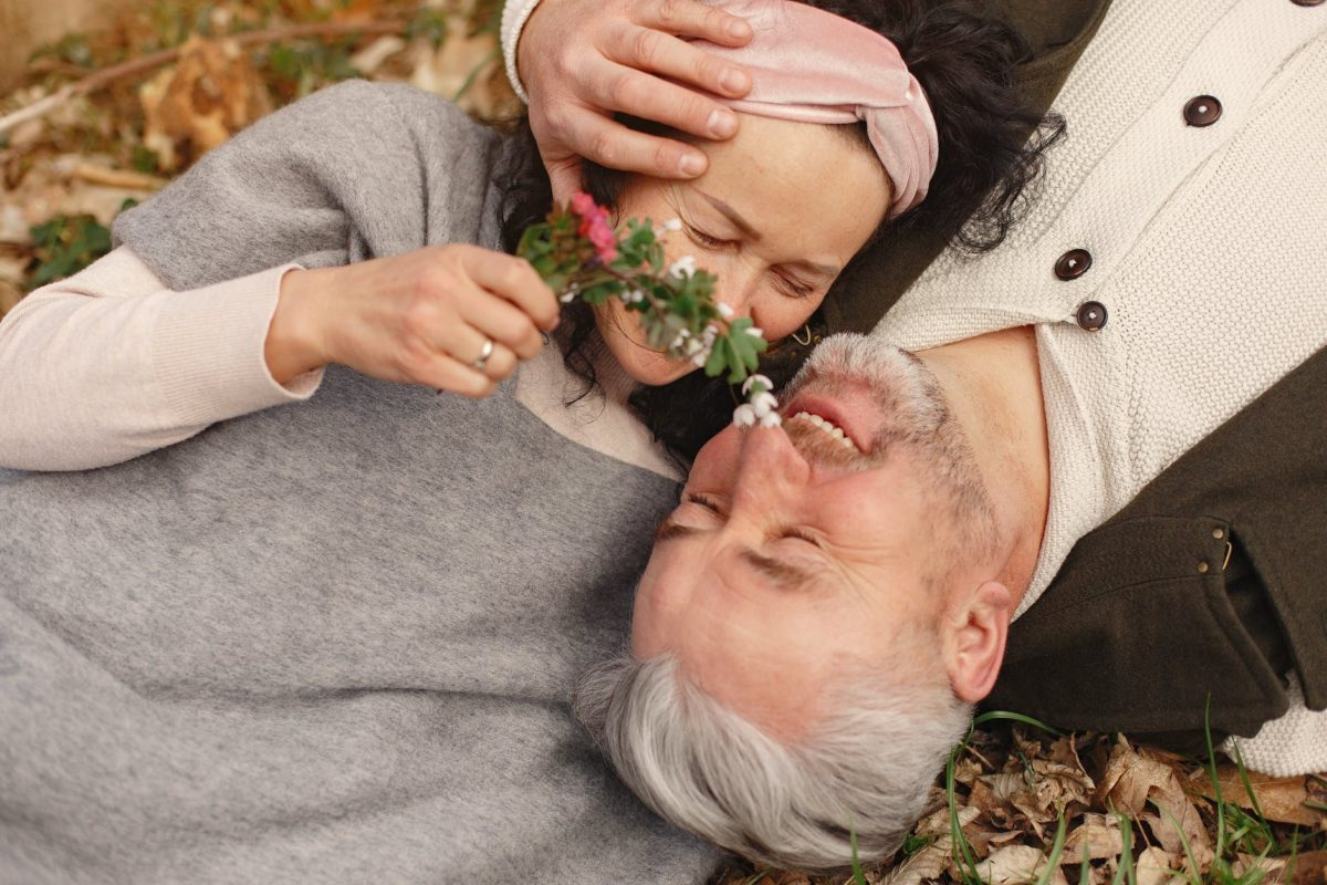 happy senior couple in love with bunch of fresh flowers in nature