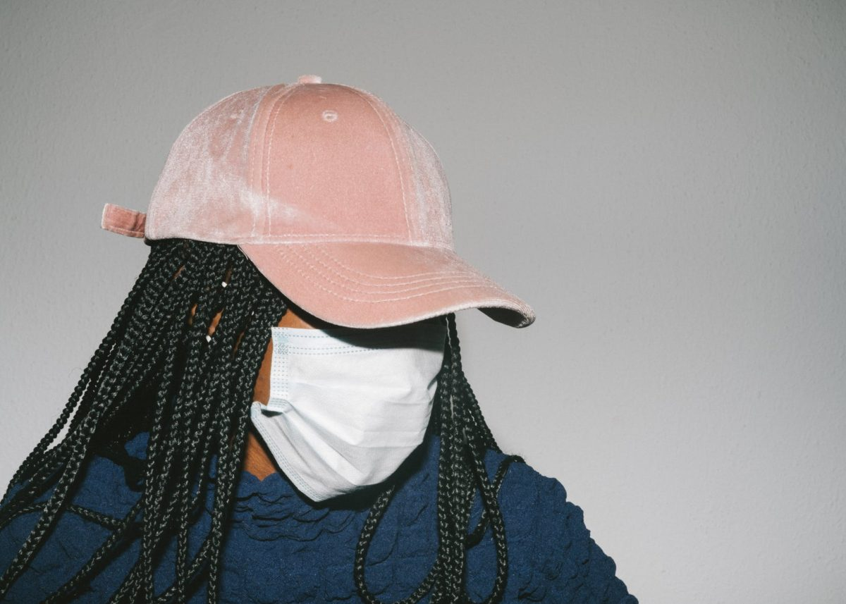 black woman in protective mask on gray background