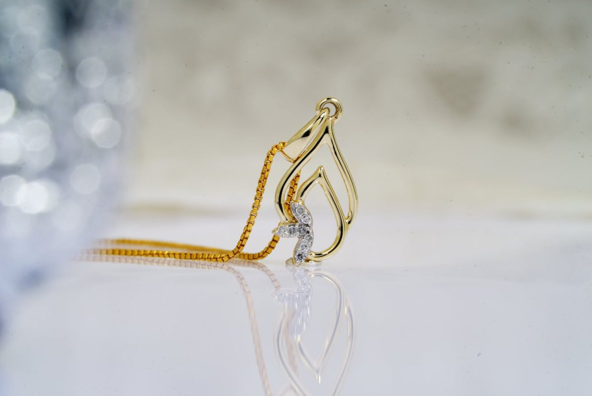 shiny golden pendant on chain on reflecting table