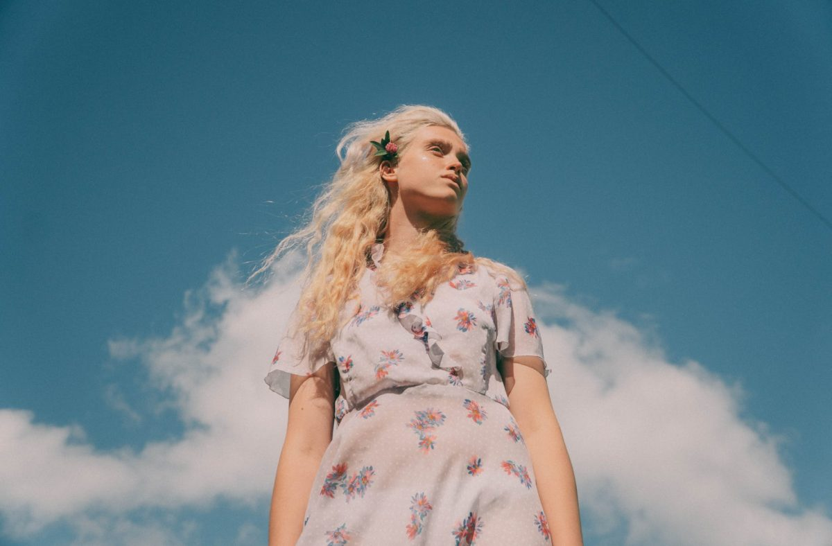 gentle woman with flower in hair under blue sky