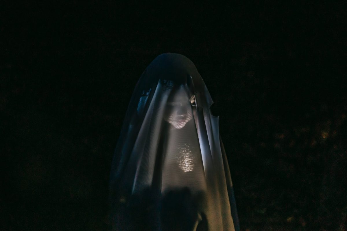 mysterious child shining flashlight on face covered with blanket