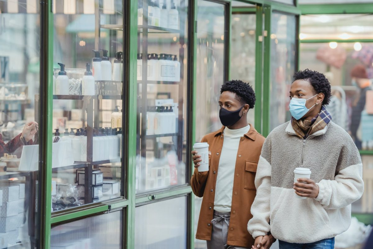 black gays in protective masks with coffee walking near showcase
