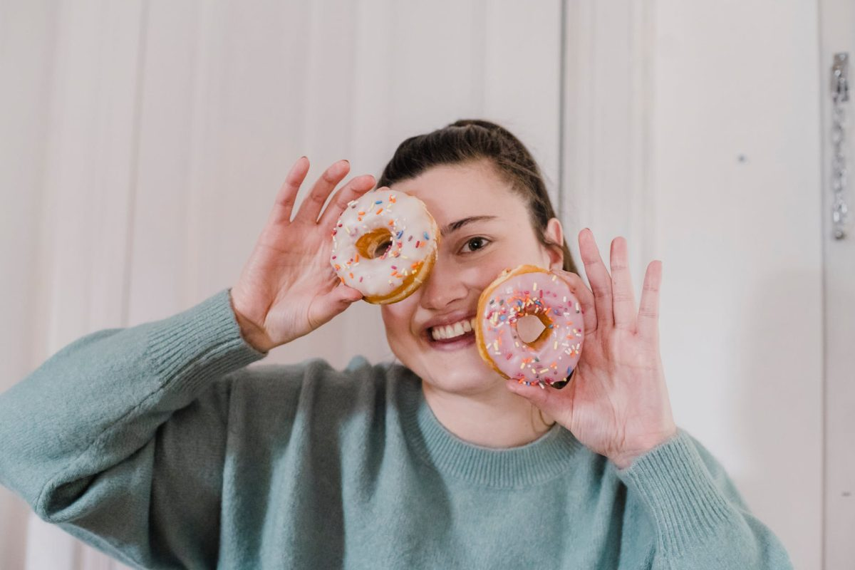 cheerful woman with tasty doughnuts