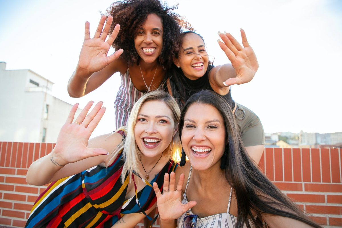smiling young diverse ladies showing hi sign while taking selfie on terrace