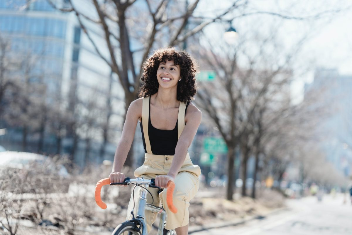 happy ethnic woman riding bicycle on street
