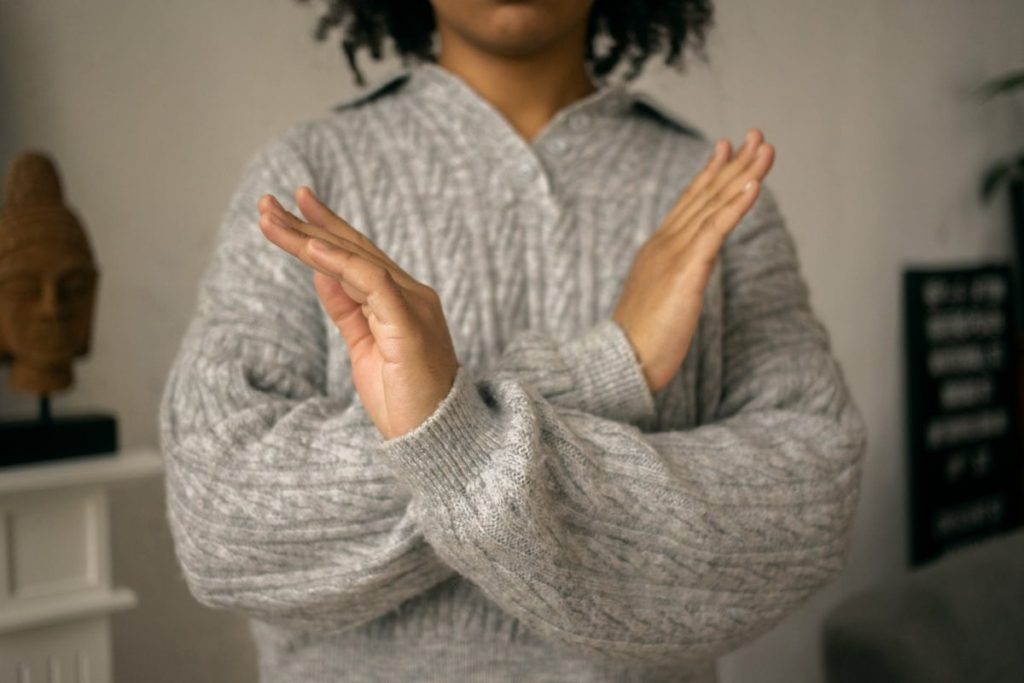 calm black woman crossed arms as restriction sign in light room