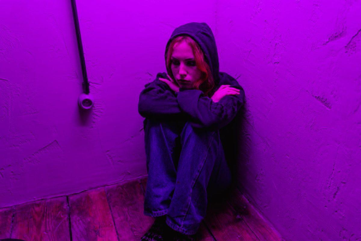 woman in black hoodie standing beside pink wall